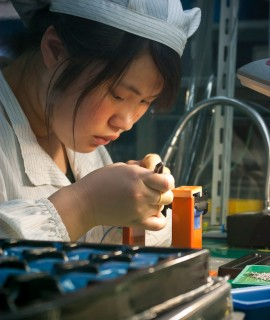 A Chinese worker putting together the lens assembly for our TEK4 digital camera in Ningbo, China.